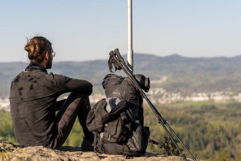 Wanderer schaut in die Ferne und sitzt neben Rucksack und Trekkingstöcke - Guide