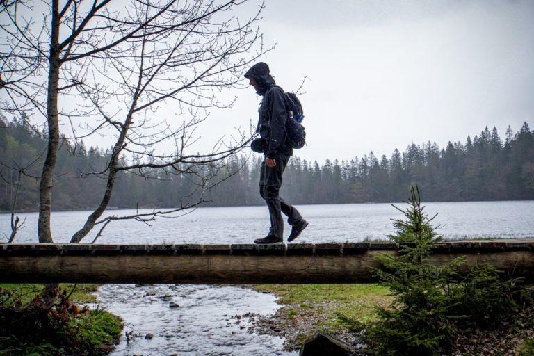 Wandern bei Regen über einen Steg am Feldsee